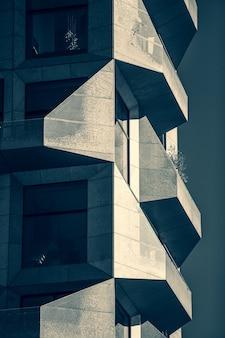 유리와 돌로 완전히 덮인 현대적인 건물의 수직 회색조 샷