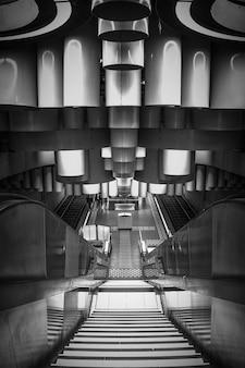 벨기에 브뤼셀에 에스컬레이터가 있는 현대적인 지하철역의 수직 그레이스케일 샷
