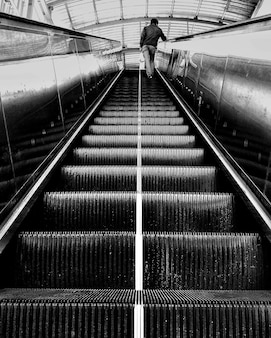 Vertical grayscale shot of a person standing on an escalator