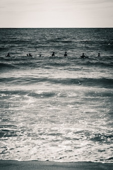 Vertical grayscale shot of  a sea with silhouettes of people