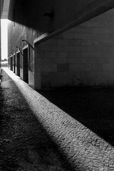 建物の歩道を照らす太陽の垂直方向のグレースケールショット