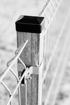 Vertical greyscale closeup shot of a  metal grid fence pole