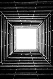 Vertical greyscale low angle shot of the light coming through the ceiling of a tall building