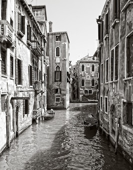 Vertical greyscale shot of a canal in the historic district of venice, italy