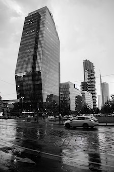 Vertical greyscale shot of a street with modern buildings in milan, italy