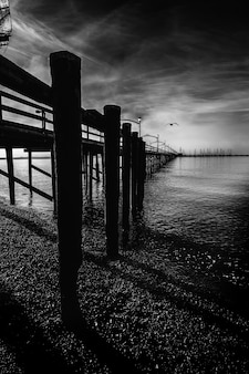 Vertical greyscale shot of a wooden dock with columns on the lake under the beautiful storm clouds