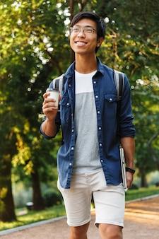 公園でラップトップコンピューターと歩く眼鏡の垂直幸せなアジア人男性学生