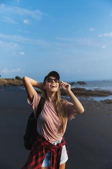 Verticale di donna viaggiatore felice guardando il sole in piedi sulla sabbia vulcanica nera.