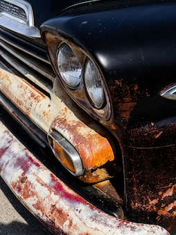 Vertical of the headlights and the bumper of an old rusty black automobile