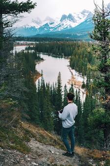 Вертикальный высокий угол фотографа-мужчины, стоящего на скале и смотрящего на реку