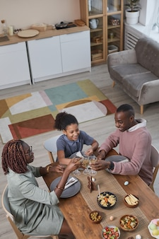 Vertical high angle portrait of modern african -american family enjoying dinner together while celebrating easter at home, copy space
