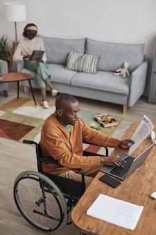 Вертикальный портрет афроамериканца с высоким углом обзора, использующего инвалидную коляску и работающего дома с детскими игрушками в фоновом режиме