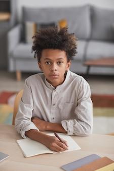 家の内部の机に座って宿題をしながらカメラを見ている10代のアフリカ系アメリカ人の少年の垂直高角度の肖像画