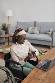 Вертикальный высокий угол портрет молодой афро-американской женщины, использующей инвалидное кресло, работая из дома с детскими игрушками в фоновом режиме