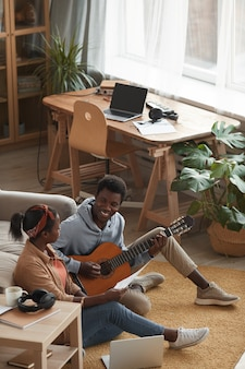 Vertical high angle portrait of two young african-american musicians playing guitar and writing music together while sitting on floor in recording studio, copy space
