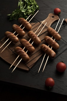 Vertical high angle shoot of barbequed sausages and cherry tomatoes on a wooden surface