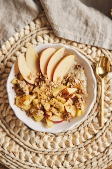 Vertical high angle shot of a bowl porridge with cereal and nuts, and slices of apple on a table