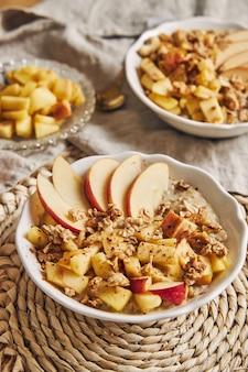 Ripresa verticale ad alto angolo di una ciotola porridge con cereali e noci e fette di mela su un tavolo