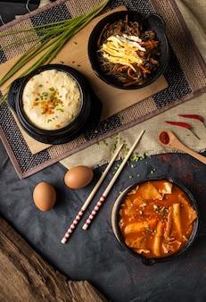 Colpo verticale ad alto angolo di ciotole di hummus e zuppa di verdure su una superficie grigia