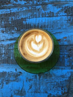 Vertical high angle shot of cappuccino on a blue wooden surface
