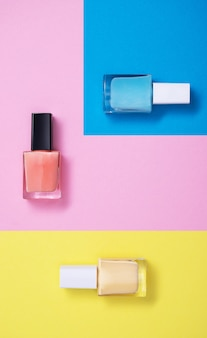 Vertical high angle shot of colorful nail polishes on a multicolor paper