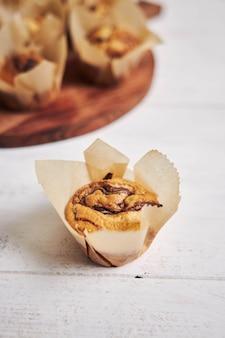 Ripresa verticale ad alto angolo di un delizioso muffin al cioccolato vicino a un piatto di legno su un piatto bianco