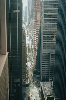 Vertical high angle shot of a long city street between modern skyscrapers
