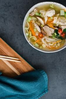 テーブルの上のいくつかの箸の横にある麺と肉のボウルの垂直ハイアングルショット
