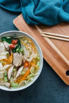 Вертикальный снимок под высоким углом: миска с лапшой и мясом рядом с палочками для еды на столе