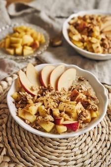 シリアルとナッツ、そしてテーブルの上のリンゴのスライスとボウルのお粥の垂直ハイアングルショット