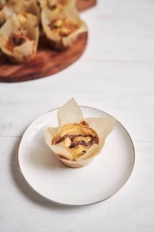 하얀 접시에 있는 나무 접시 근처에 있는 맛있는 초콜릿 머핀의 수직 하이 앵글 샷
