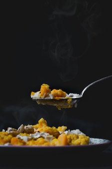 쌀, 닭고기, 노란 소스와 함께 맛있는 뜨거운 요리의 세로 높은 각도 샷