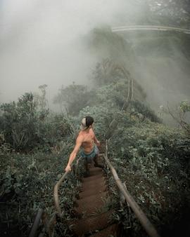 계단에 서서 안개가 자욱한 산을 내려다 보는 남성의 수직 높은 각도 샷