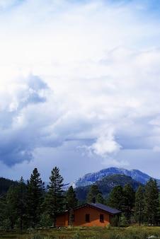 Tuddal gaustatoppenの曇り空の下の丘の小さな家の垂直ハイアングルショット