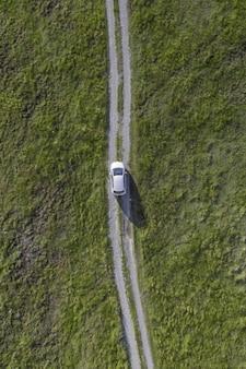 緑の谷の小道を通る白い車の垂直ハイアングルショット