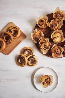Вертикальный снимок под высоким углом восхитительных шоколадных кексов и свежих пончиков на белом столе