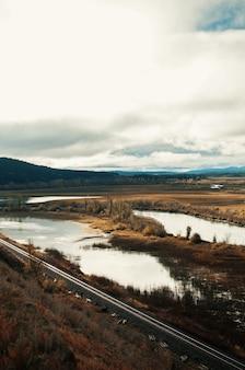 曇り空の下の谷にある小さな池の垂直ハイアングルショット