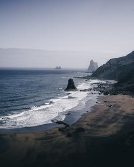 Вертикальный снимок с высоким углом каменистого берега моря в пасмурный день