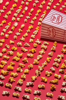 Vertical high angle shot of a paper popcorn cup and popcorns scattered on a red surface