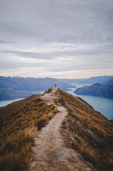 Vertical high angle shot of a person standing on the end of walking road on roys peak in new zealand