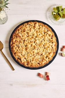 Colpo verticale ad alto angolo di un piatto di crostata di torta croccante rhabarbar e alcuni ingredienti su un tavolo