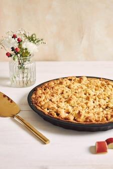 Ripresa verticale ad alto angolo di un piatto di crostata di torta rhabarbar croccante e alcuni ingredienti su un tavolo