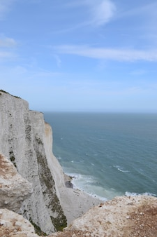Vertical high angle shot of rocky cliffs near the sea in dove, england
