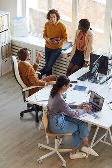 Вертикальный вид под большим углом на многонациональную команду ит-разработчиков, сотрудничающую над бизнес-проектом во время работы в студии производства программного обеспечения