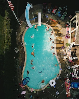 Vertical high angle view of a pool during a party under the sunlight in the us