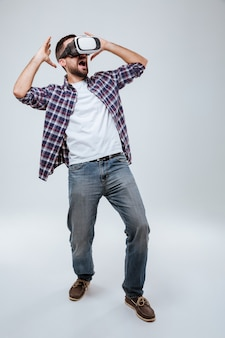 Vertical image bearded man in shirt using virtual reality device