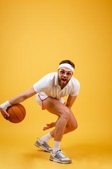 Immagine verticale di sportivo barbuto in occhiali da sole giocando a basket