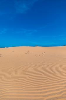 L'immagine verticale delle bellissime dune di sabbia di mui ne, vientam sotto un cielo blu chiaro