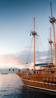 Vertical image of beautiful wooden historical ship in port at sunset light rays