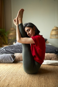 Vertical image of beautiful young woman in sportswear practicing ashtanga yoga, sitting in urdhva mukha paschimottanasana or upward facing intense stretch pose, embracing legs, having relaxed look